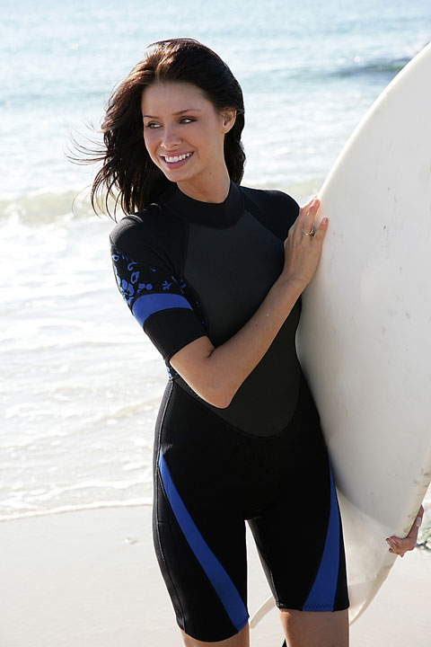 young woman surfer wearing a shortie wetsuit