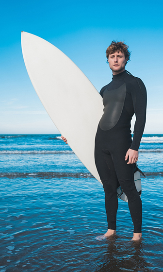 surfer wearing a full wetsuit and carrying a surfboard